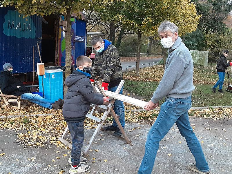 Betreuer und Jugendliche am Holzverarbeiten
