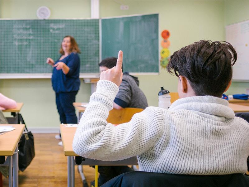 Junge im Klassenraum, der sich meldet